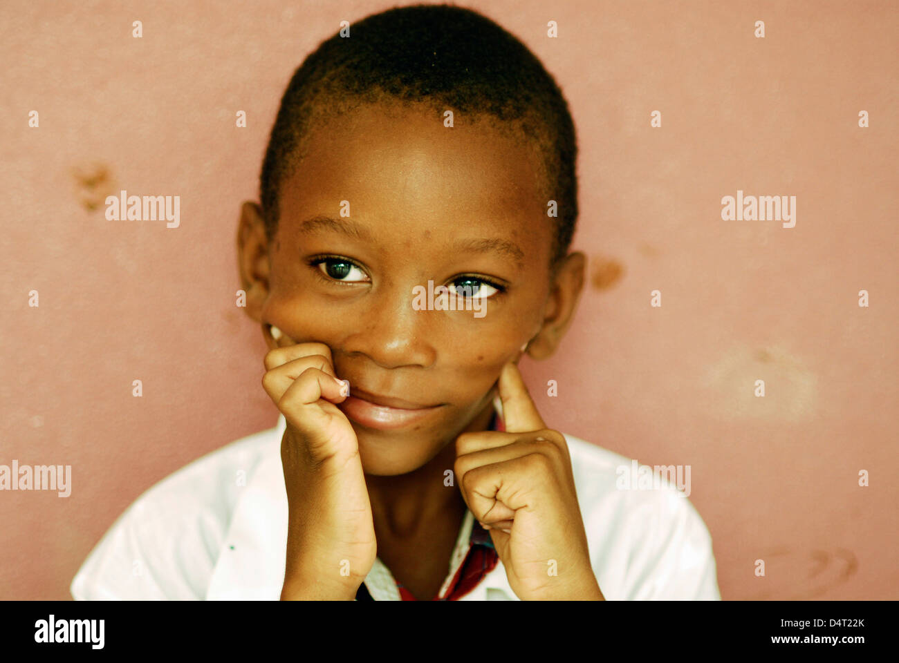 Africa, Angola, Luanda, close-up portrait of an African boy in a white shirt smiling in front of a wall. (MR) - Stock Image
