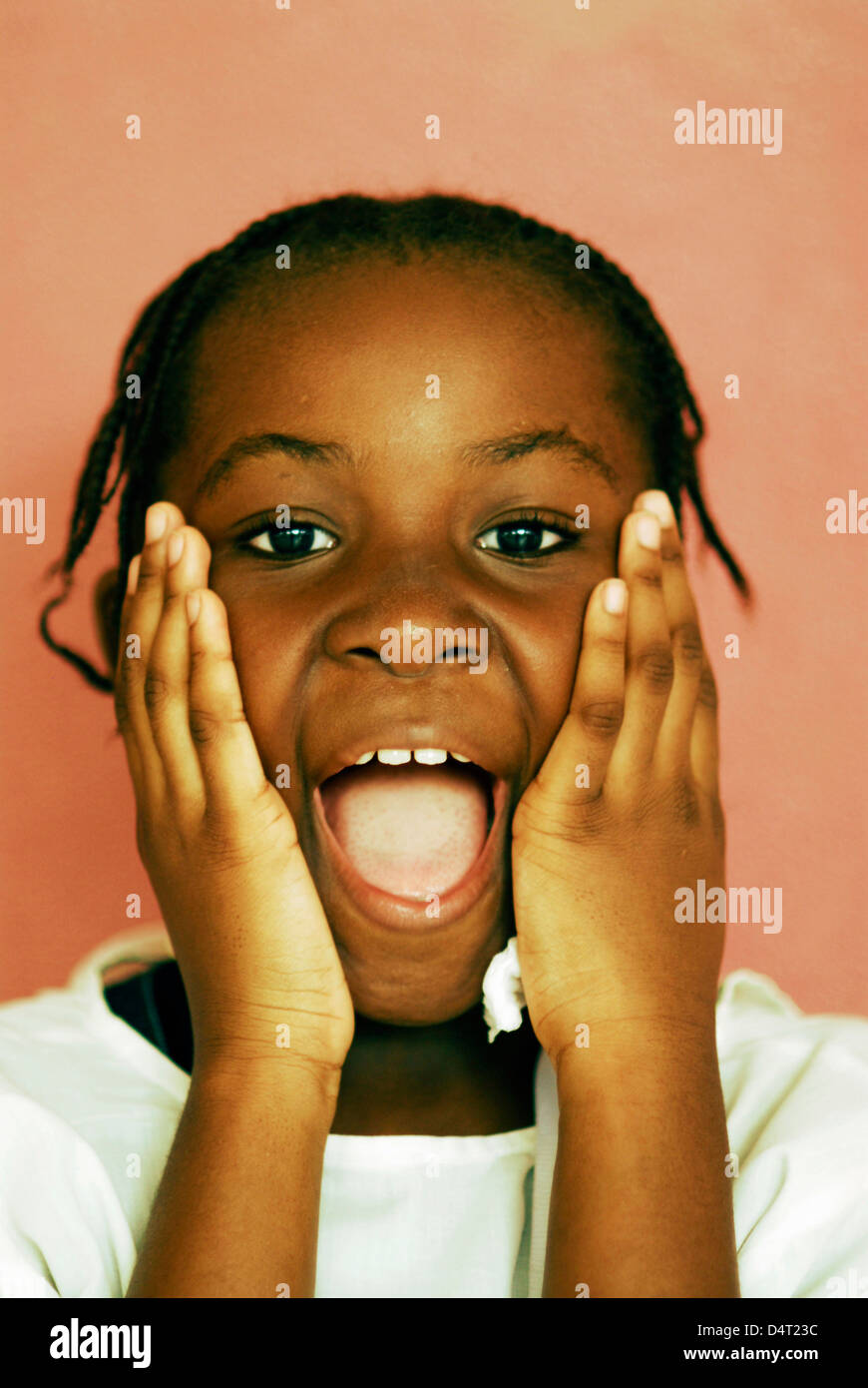 Africa, Angola, Luanda, portrait of a little African girl with her mouth open standing in front of a wall - Stock Image