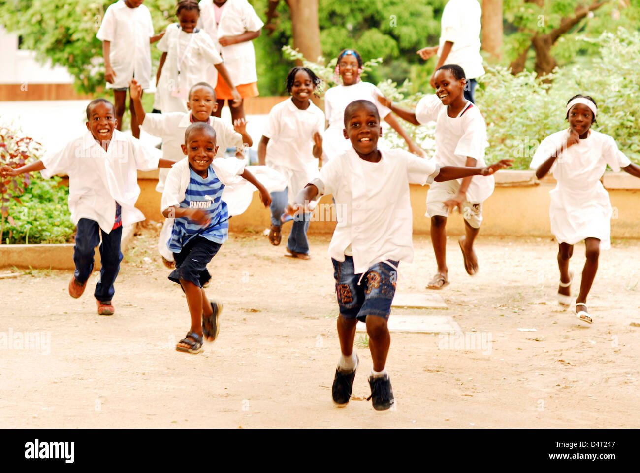 Angola, Luanda, group of African school children running together at a playground with trees in the background. - Stock Image