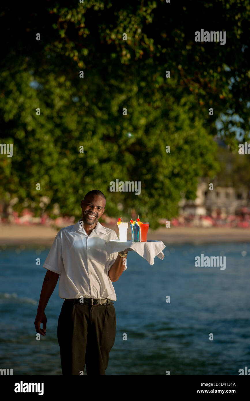 A waiter holding a tray of cocktail drinks on the west coast of Barbados, Holetown (Sandy Lane in background) - Stock Image