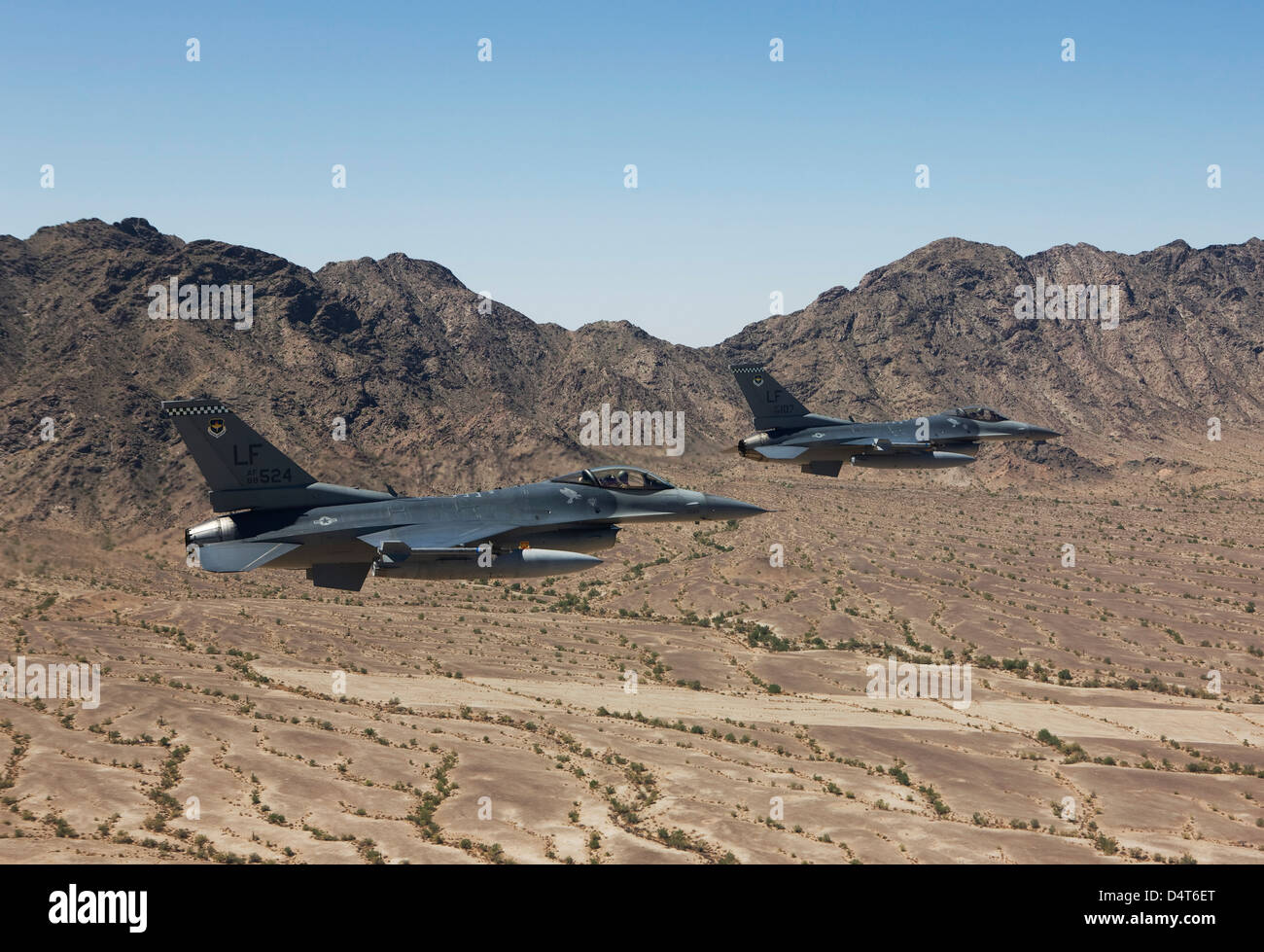 Two F-16's fly in formation over the Arizona desert. - Stock Image
