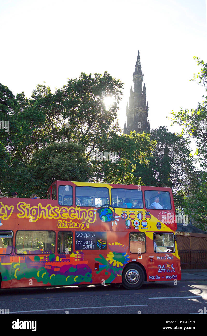 city tour bus parked by waverley station with tip of scott monument to rear - Stock Image