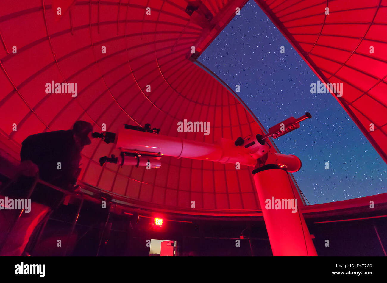 Inside the observatory, an astronomer makes observations with a large refractor telescope at the 3RF astronomy campus - Stock Image