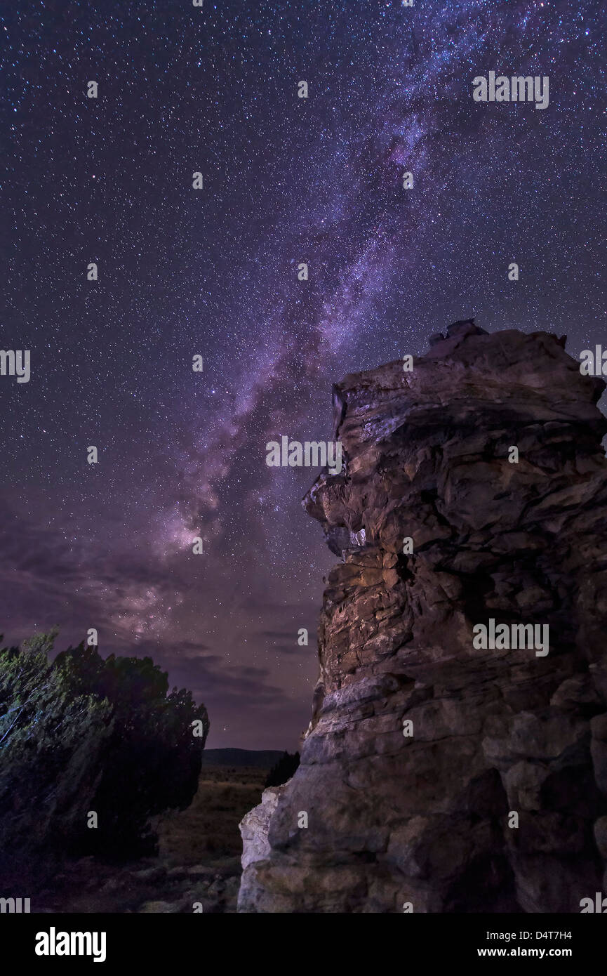 A rocky hoodoo stands against the night sky as the Milky Way sets near Black Mesa, Oklahoma. - Stock Image