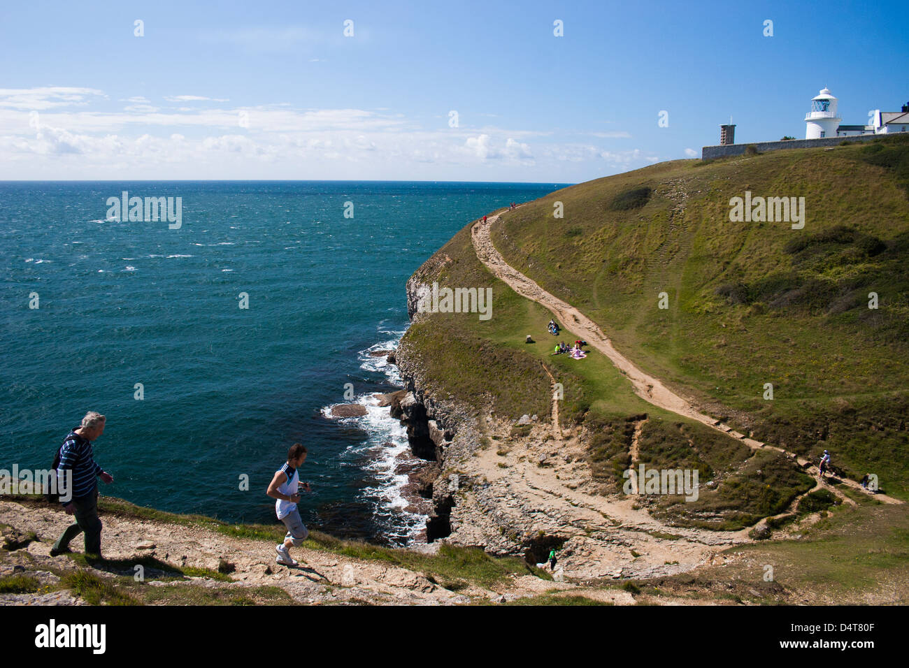 Pathway leading to Anvil Point Lighthouse along the Dorset coastline in the South of England. Walkers and joggers - Stock Image