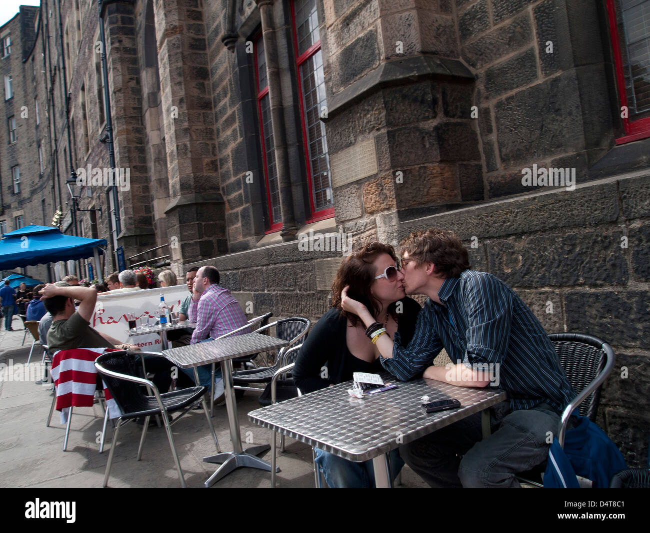 young lovers kissing at outdoor cafe - Stock Image