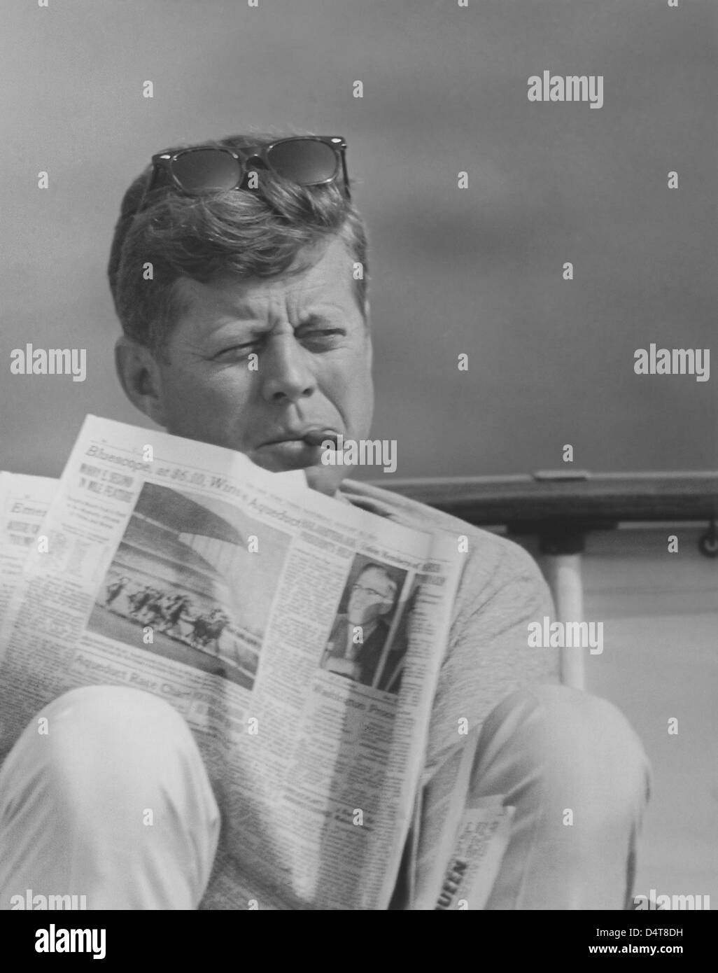 Digitally restored vintage photo of President John F. Kennedy relaxing outside, smoking a cigar and reading the - Stock Image