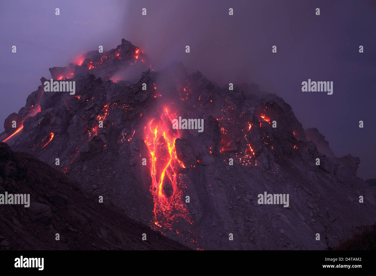 November 30, 2012 - Glowing Rerombola lava dome with incandescent rockfall deposit, Paluweh volcano, Flores, Indonesia. - Stock Image