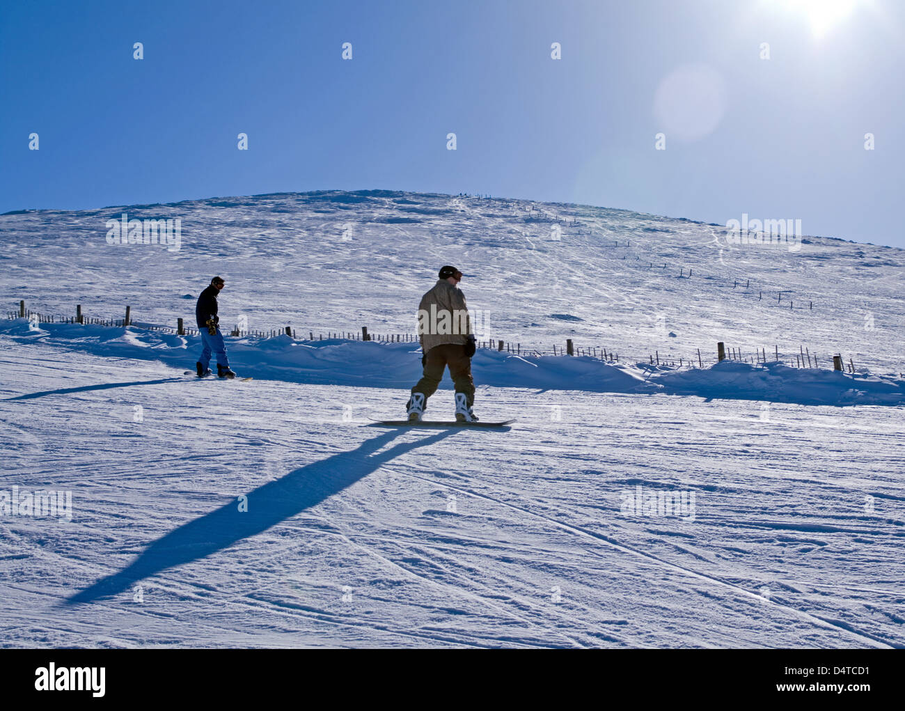 2 snowboarders on ski run, Cairngorm Mountain,  marker posts to Cairngorm summit visible behind - Stock Image