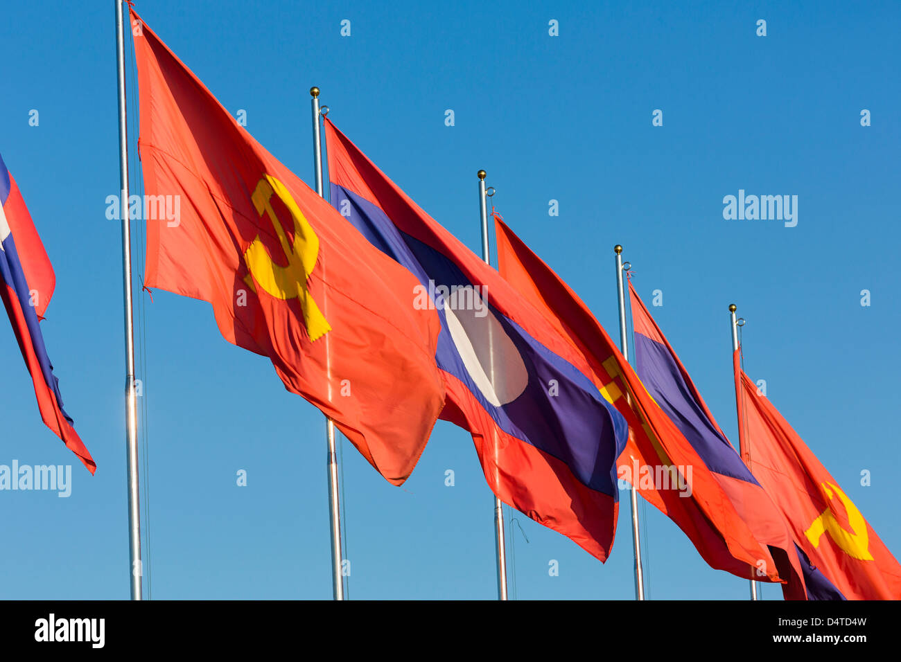 Laotian and communist flags in Vientiane, Laos - Stock Image