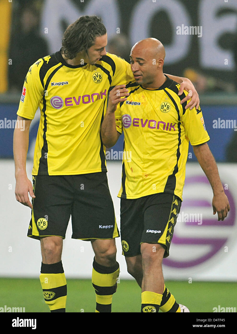 Dortmund?s Neven Subotic accompanies Dede who has to leave the field after harming himself in a duel during the - Stock Image