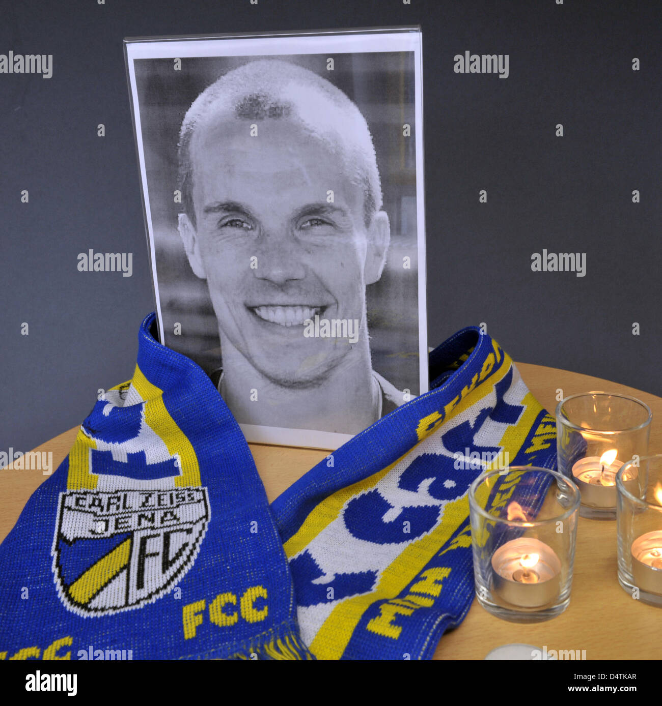 A photography, a fan scarf and candles commemorate Germany