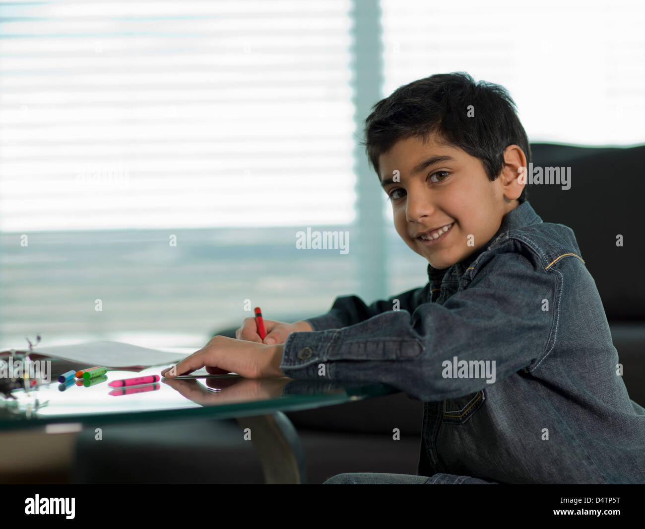 Boy Coloring With Crayons At Desk