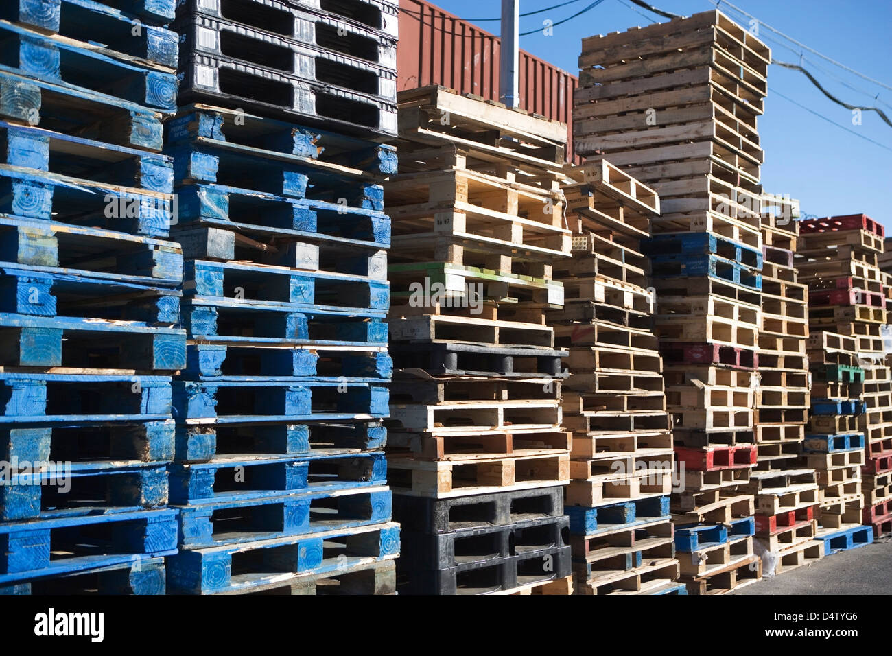Pallets stacked together in yard - Stock Image