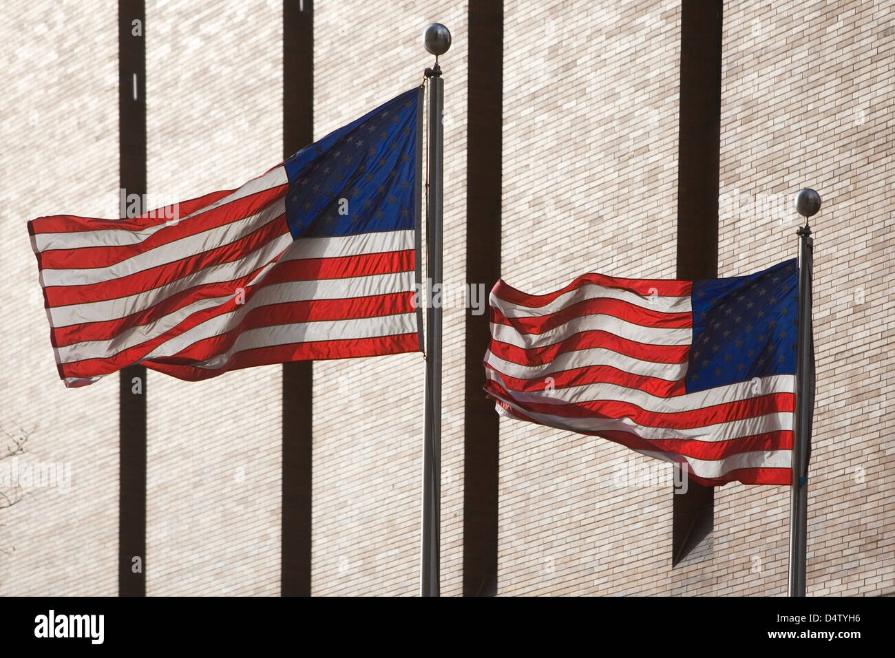American flags flying by skyscraper - Stock Image