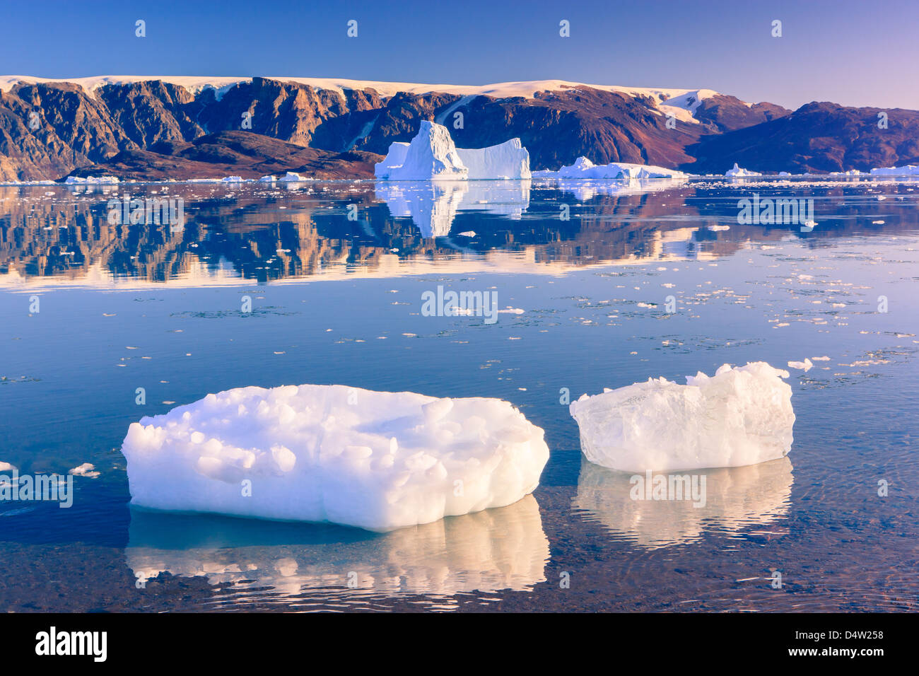 Cruising between the icebergs at Røde Ø, Scoresbysund, Greenland - Stock Image