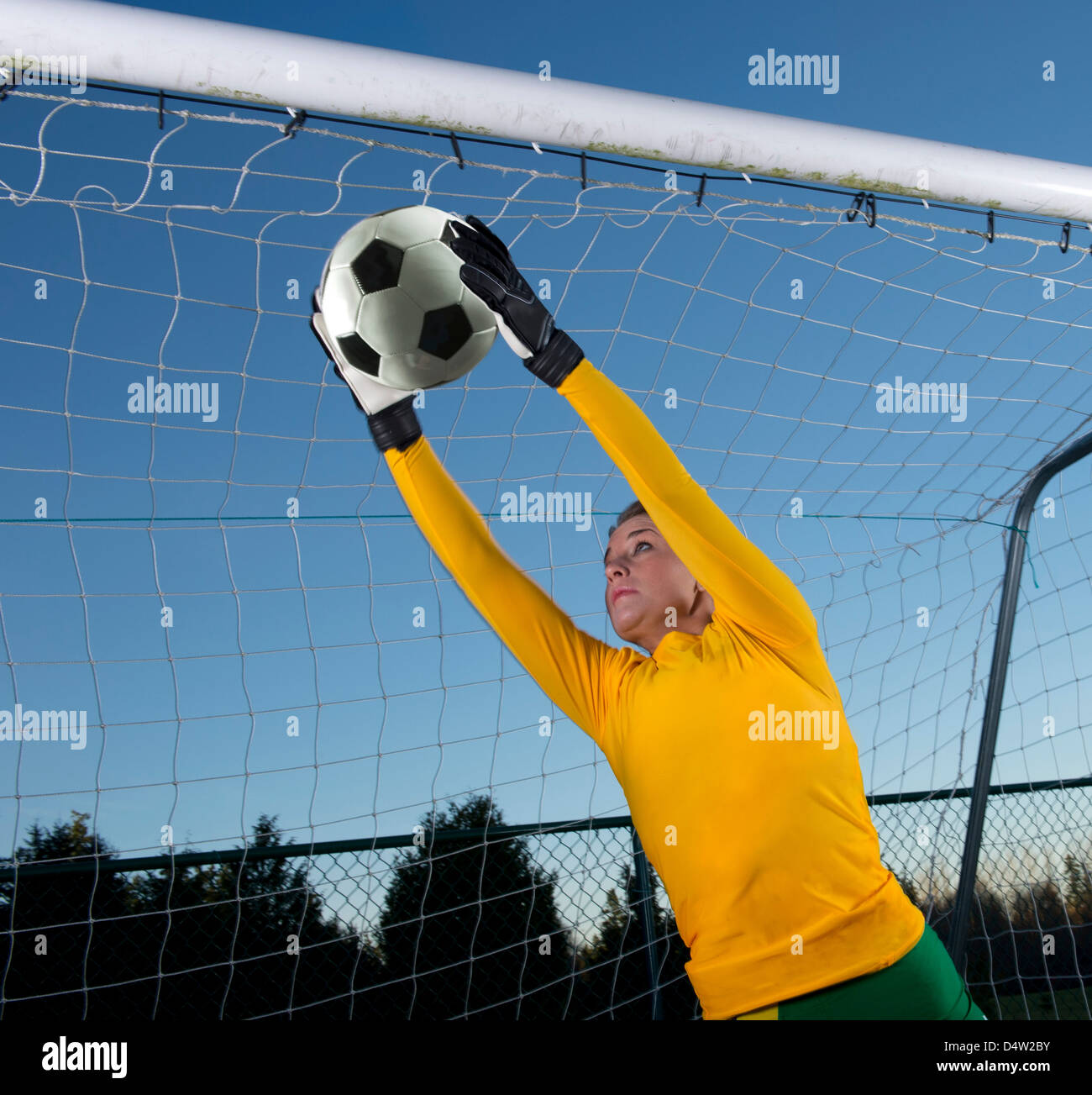 Soccer player catching ball in goal - Stock Image