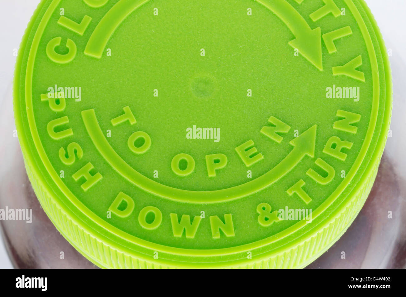 Top of a green twist off cap to a brown pill bottle. Includes arrows and the wording,'Push Down & Turn', - Stock Image