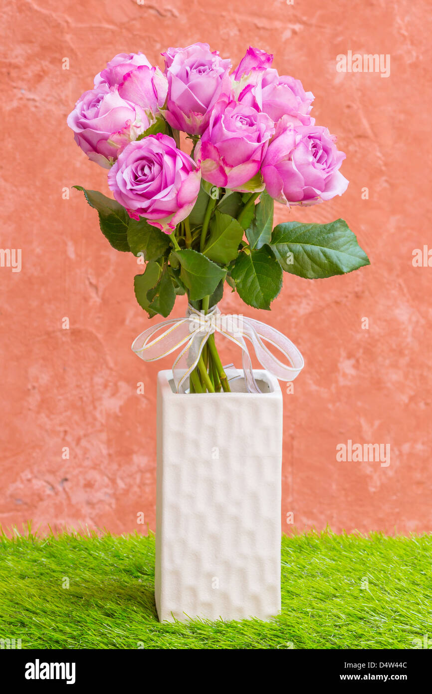 Violet rose in vase with white bow tie - Stock Image