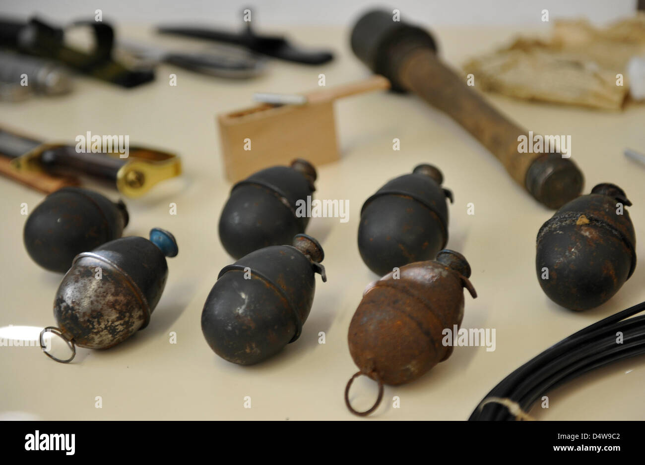 Hand grenades and a stick grenade are featured on a table during a