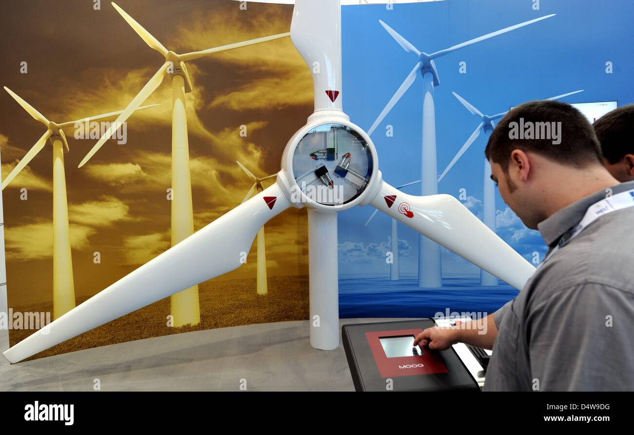 Visitors examine an exhibit at the stand of the Moog company at the Husum Wind Energy trade fair in Husum, Germany, - Stock Image