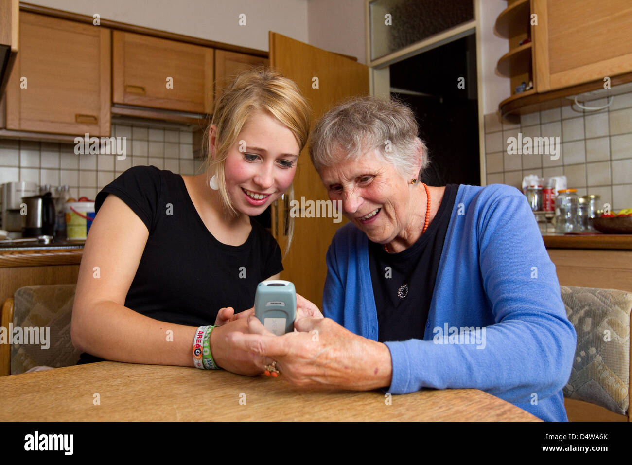 Senior Klara Fuerst (78) and student Sarah Boehm (20) use a mobile phone in their kitchen in Muenster, Germany, Stock Photo