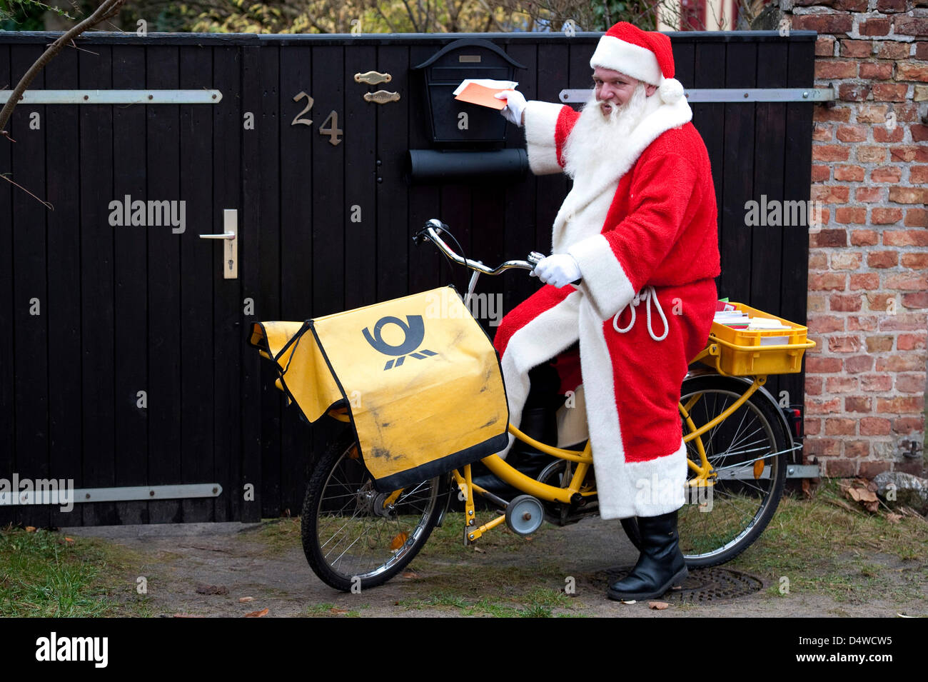 A postman wearing a santa claus costume rides on a bike in Himmelpfort, Germany, 17 November 2010. The German post - Stock Image