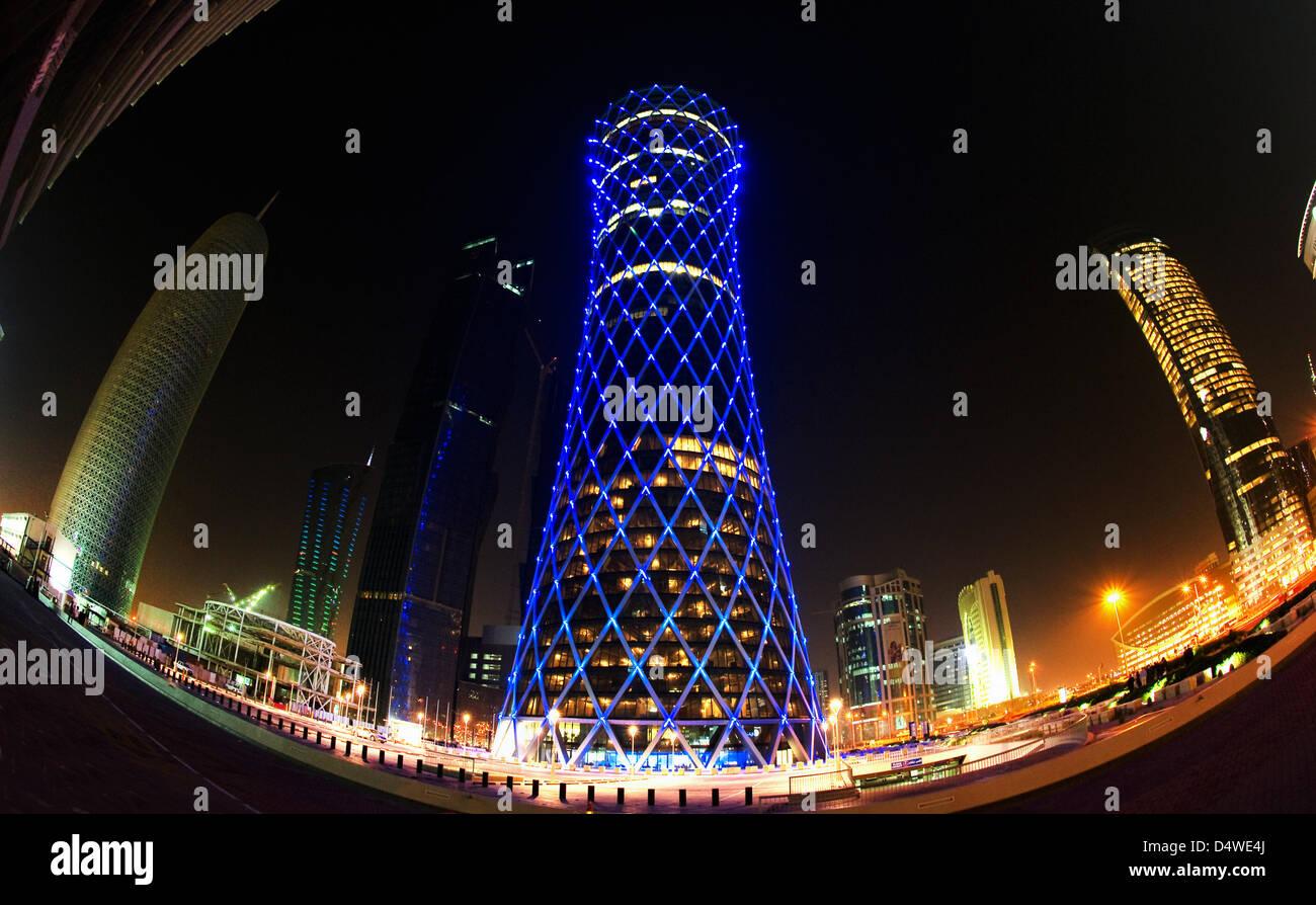In blauem Licht erstrahlt am Mittwoch (24.11.2010) der 'Qipco Tower' in Doha, Katar, zwischen weiteren Hochhäusern - Stock Image