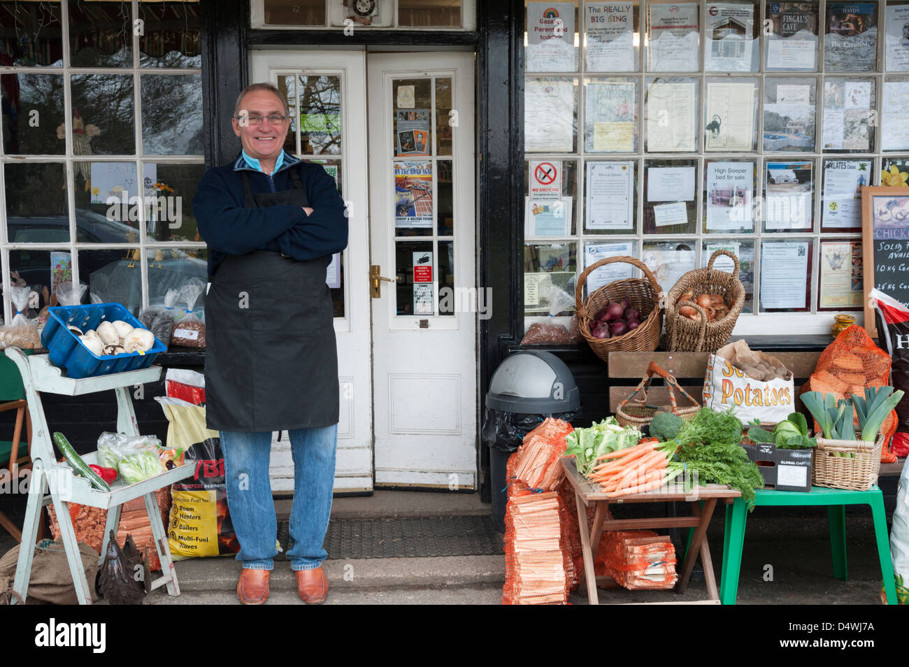 The Moulton village stores a traditional general stores and post office in Suffolk UK with the shopkeeper standing - Stock Image