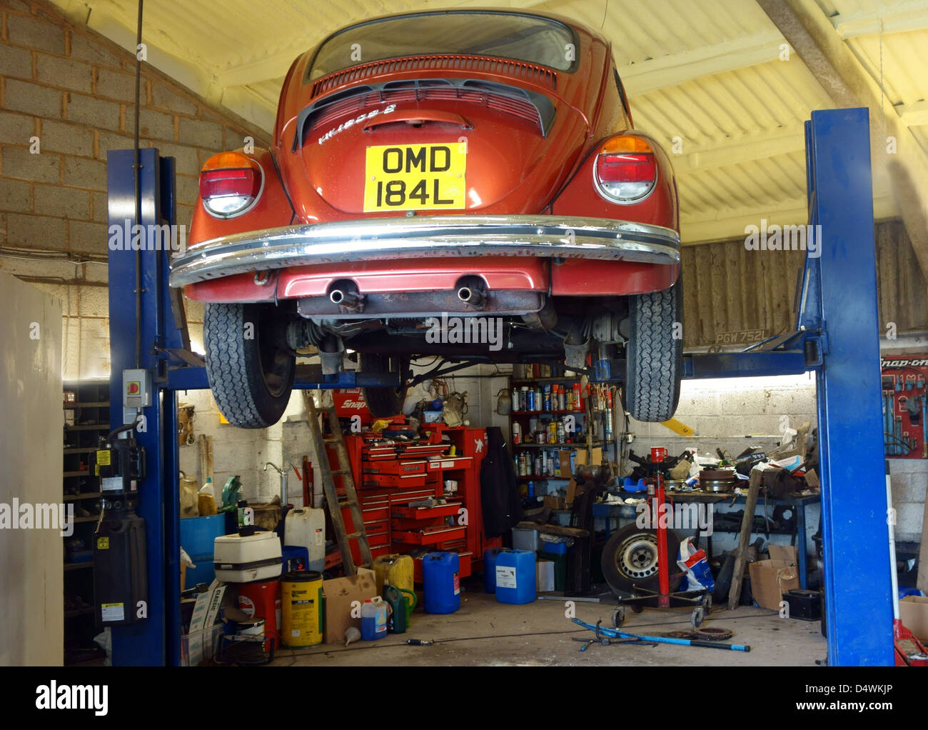 Classic VW Beetle on ramp in garage in Somerset, England - Stock Image