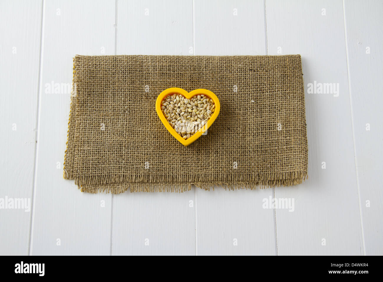 Raw pearl barley nestled in a heart, sitting on burlap and white wooden boards - Stock Image