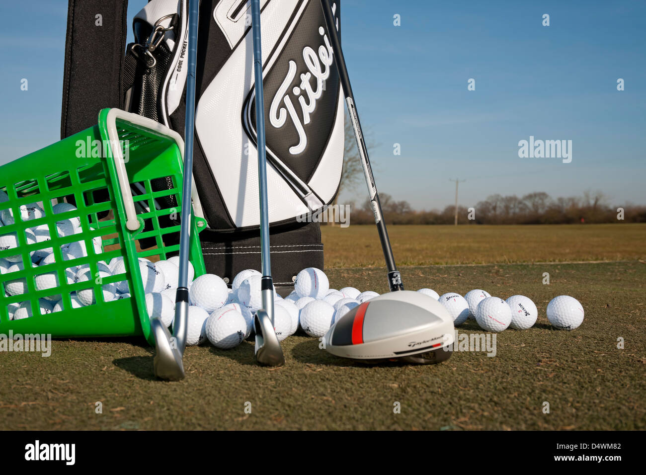 Golf bag and clubs with range balls on a golf practice ground England UK United Kingdom GB Great Britain - Stock Image