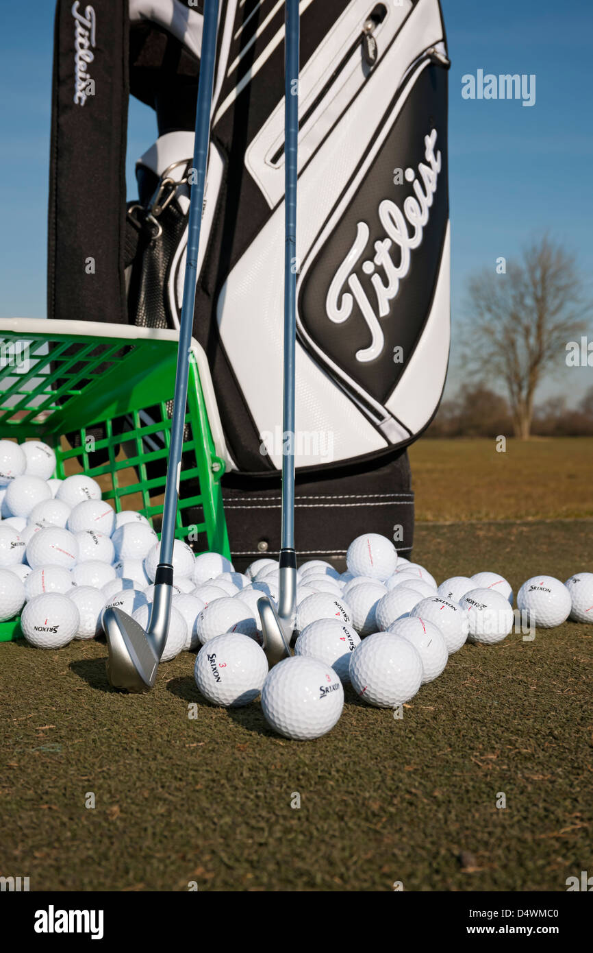 Titleist golf bag and clubs with range balls on a golf practice ground England UK United Kingdom GB Great Britain Stock Photo