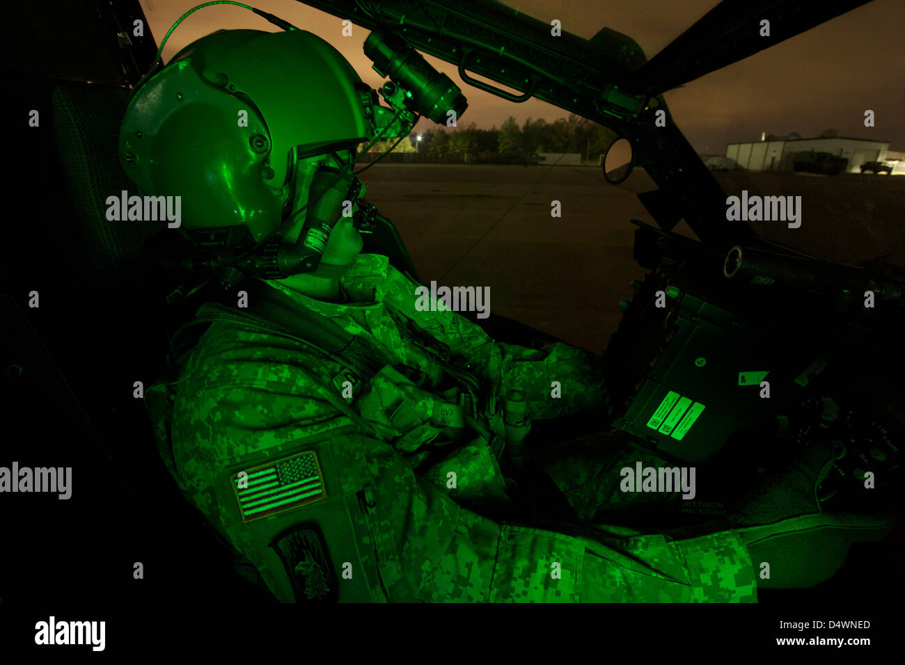 A pilot equipped with night vision goggles in the cockpit of an AH-64 Apache helicopter. - Stock Image