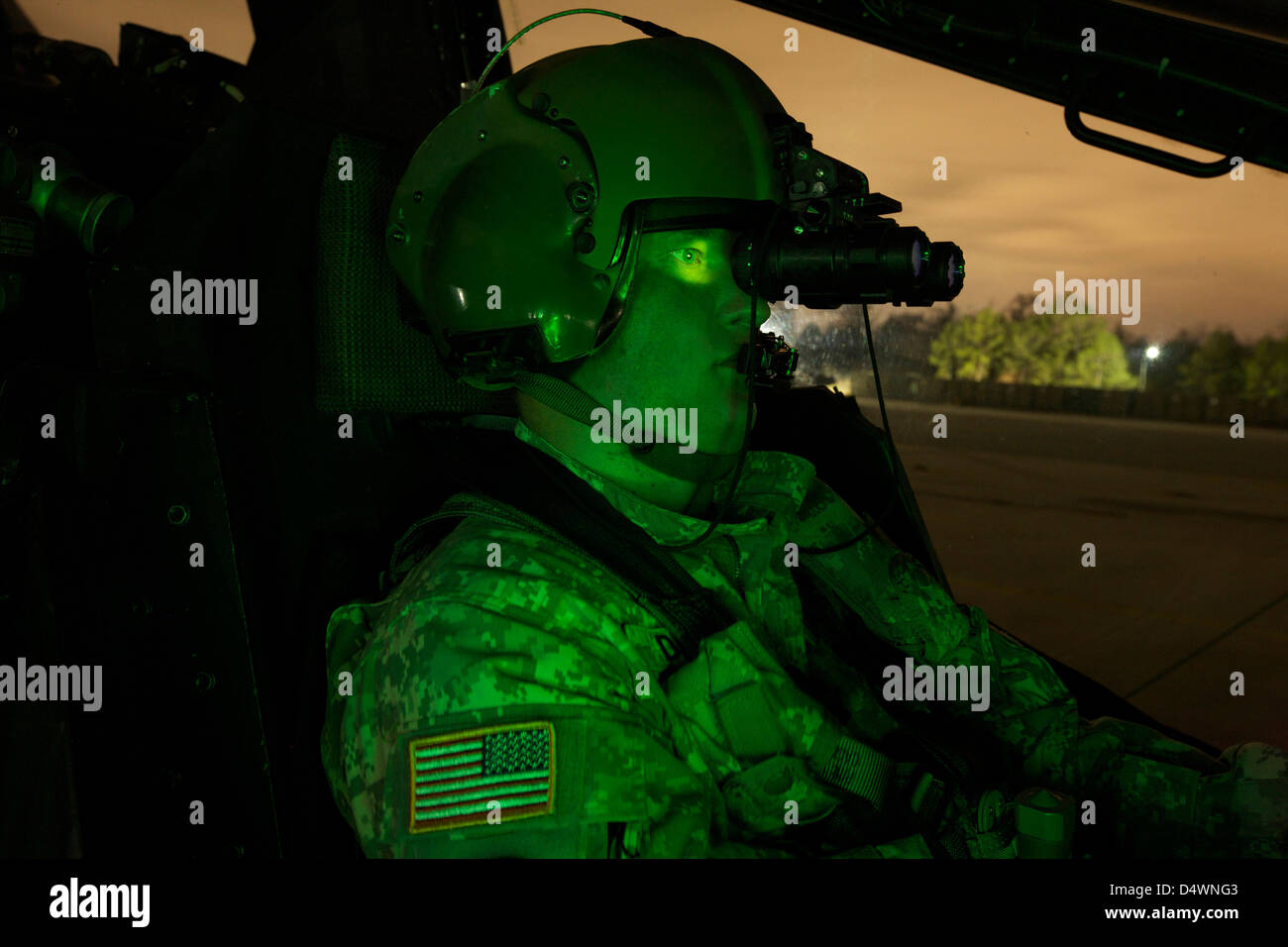 A pilot equipped with night vision goggles in the cockpit