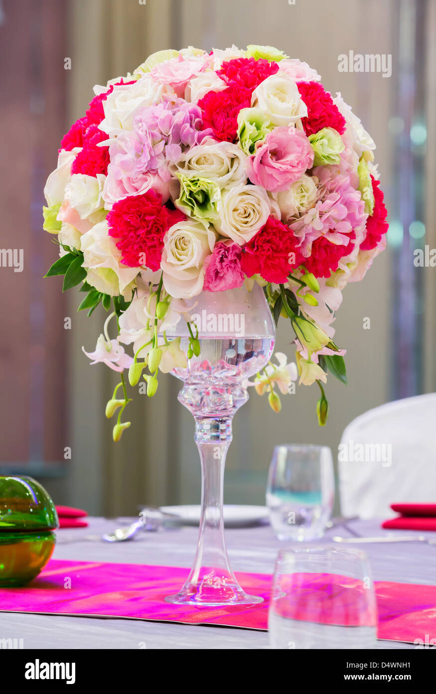 Flower bouquet in glass vase on dining table - Stock Image