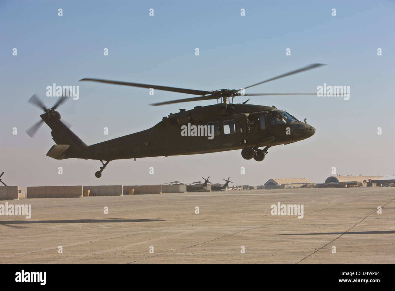 A UH-60 Black Hawk helicopter landing at a military base in Iraq. - Stock Image