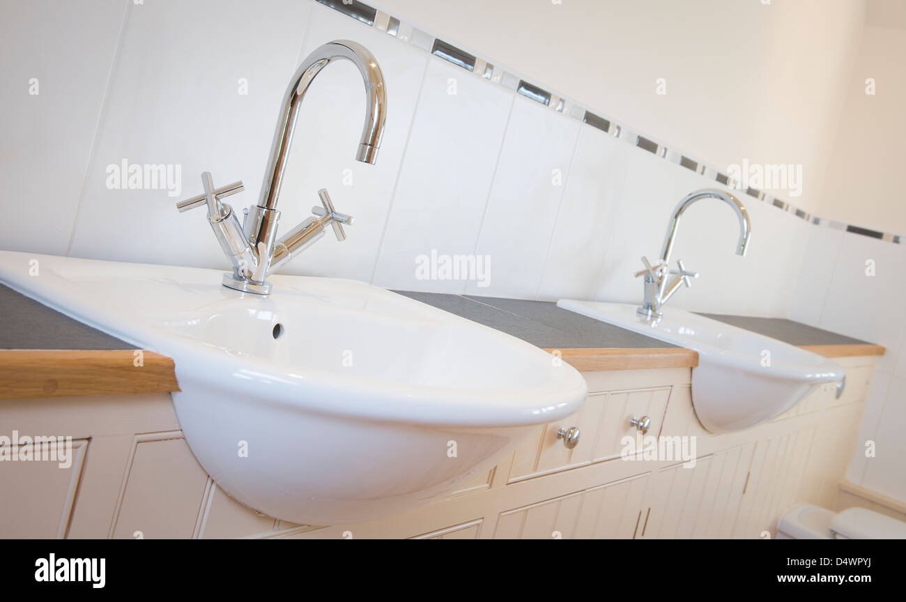Close up of his and her sinks in a newly decorated bathroom. - Stock Image