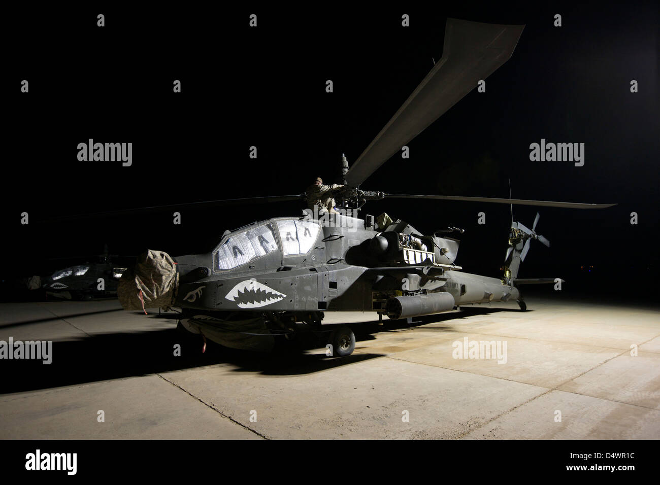 Maintenance crew work on an AH-64D Apache Longbow at night on a military base in Iraq. - Stock Image