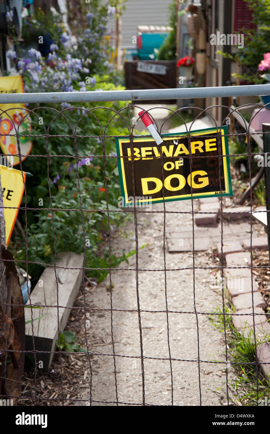 Gate with beware of dog sign attached to it and garden path beyond - Stock Image