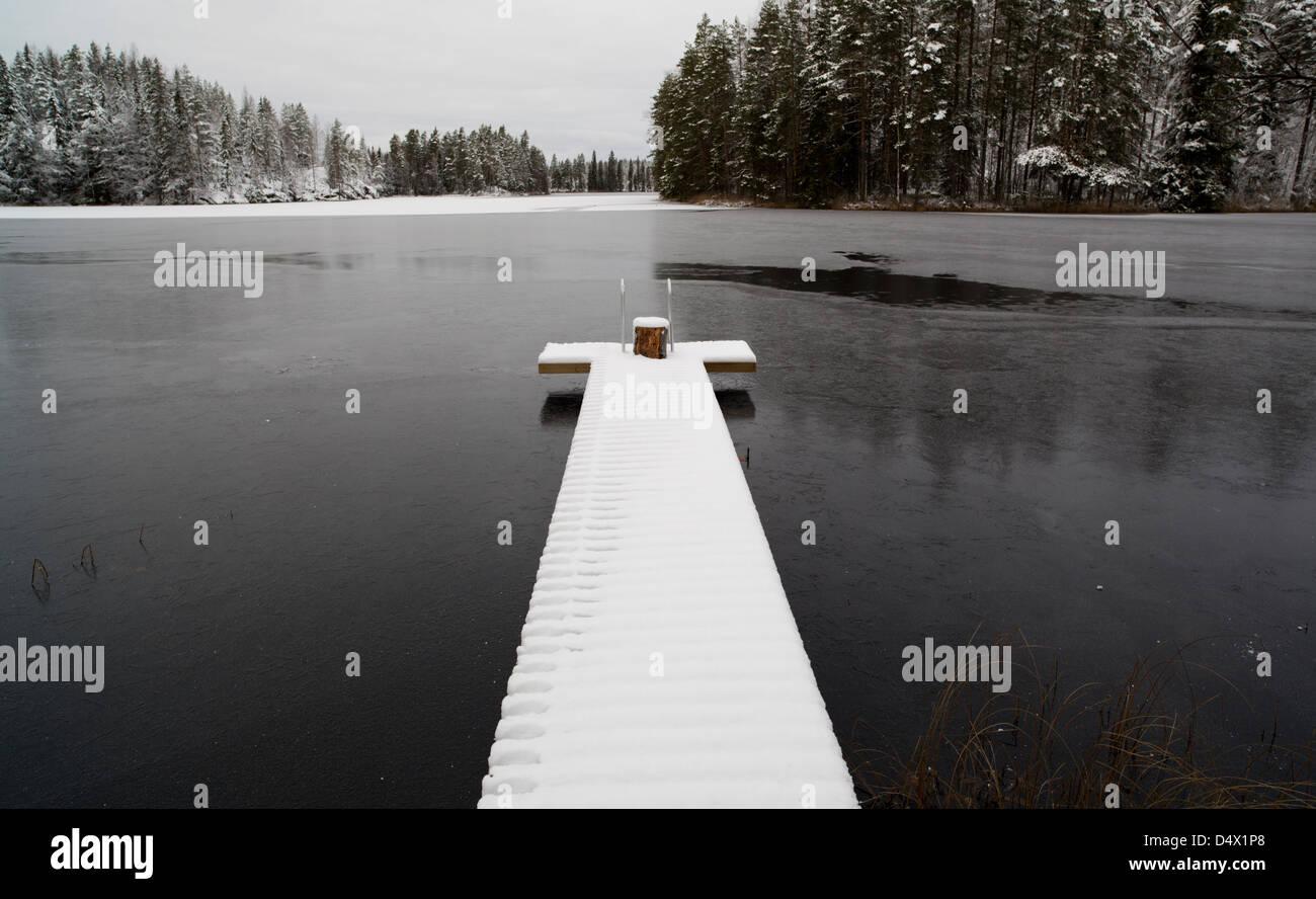 Snowy pier at freezing lake , Finland - Stock Image