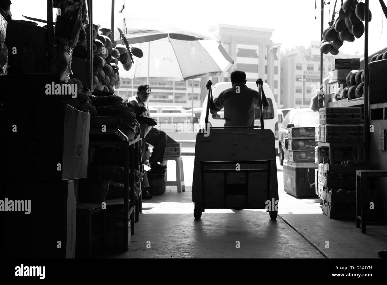 Silhouette of man pulling cart at market in Dubai, United Arab Emirates - Stock Image