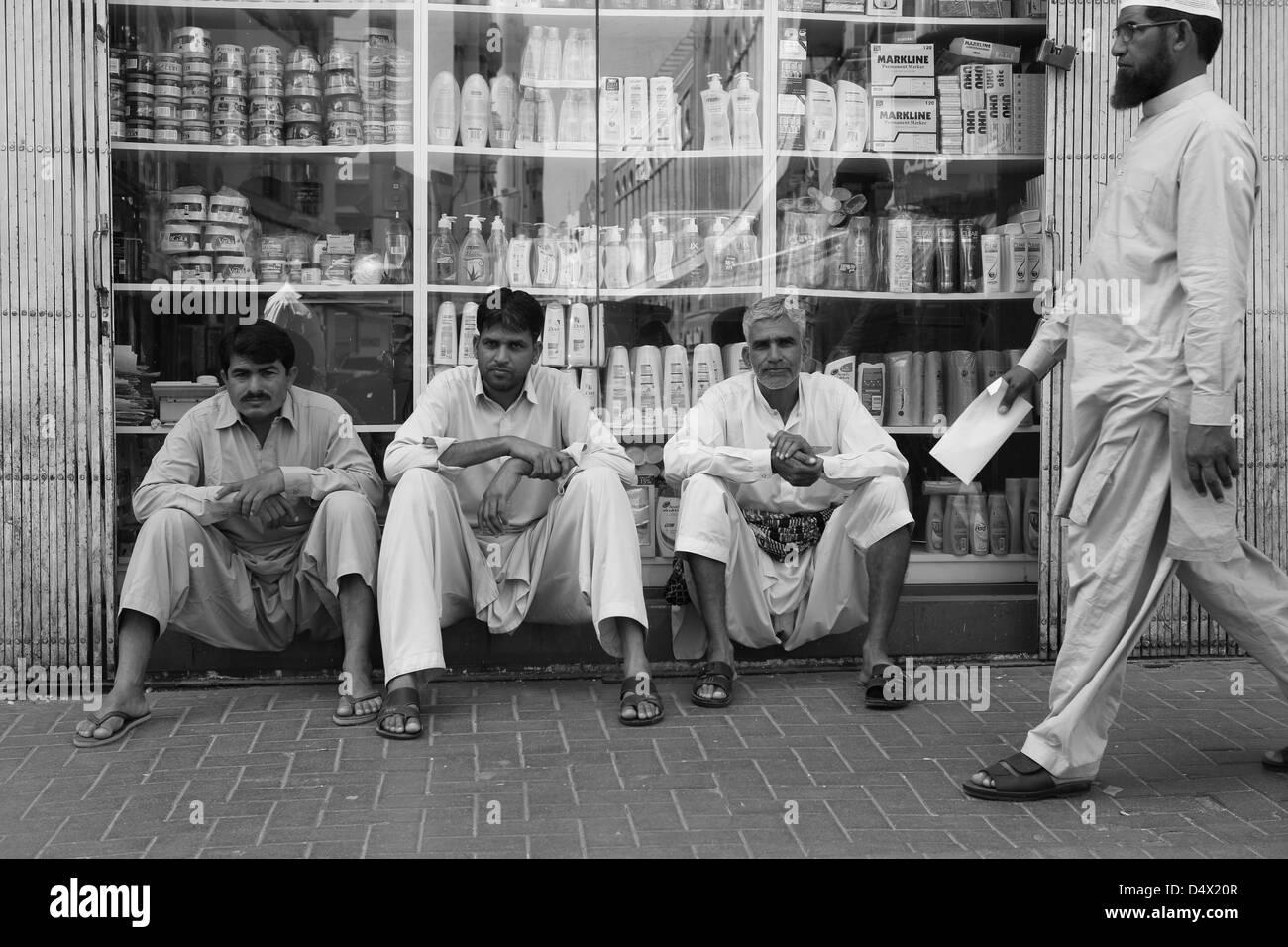 Three men sitting in front of shop window, Dubai, United Arab Emirates - Stock Image