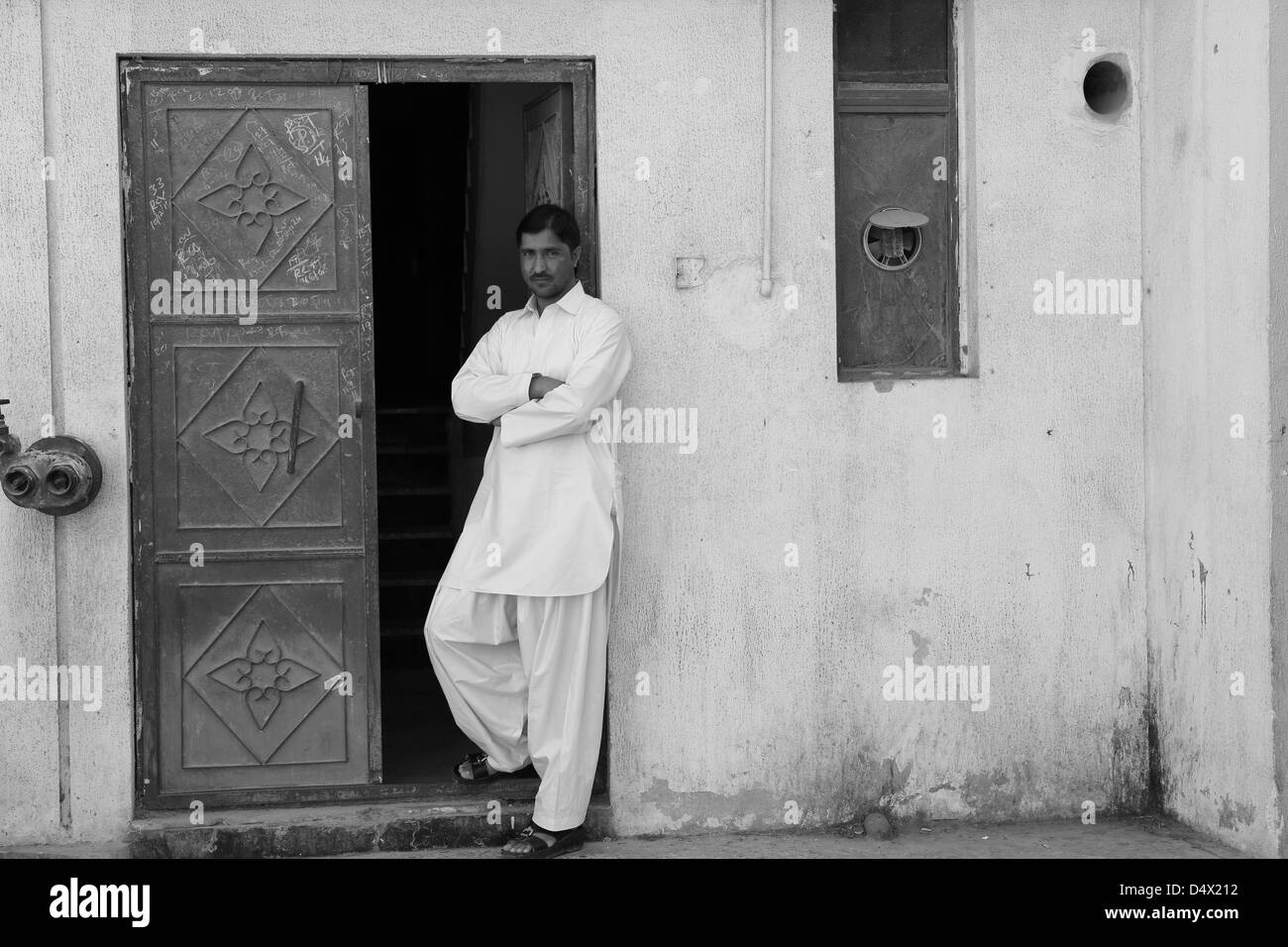 Portrait of shop owner standing in doorway, Dubai, United Arab Emirates - Stock Image