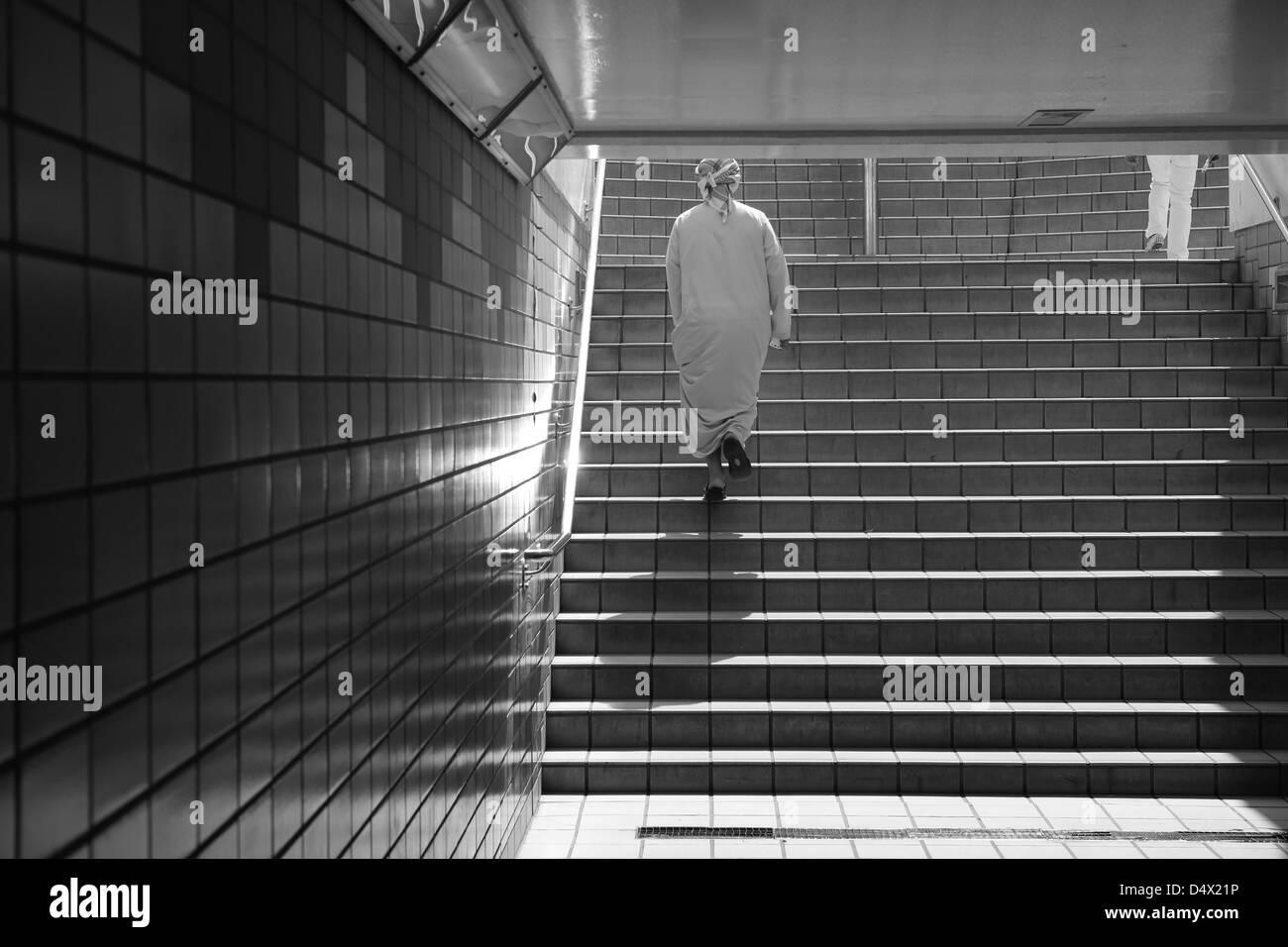 Man walking up stairs from underground walkway, Dubai, United Arab Emirates - Stock Image
