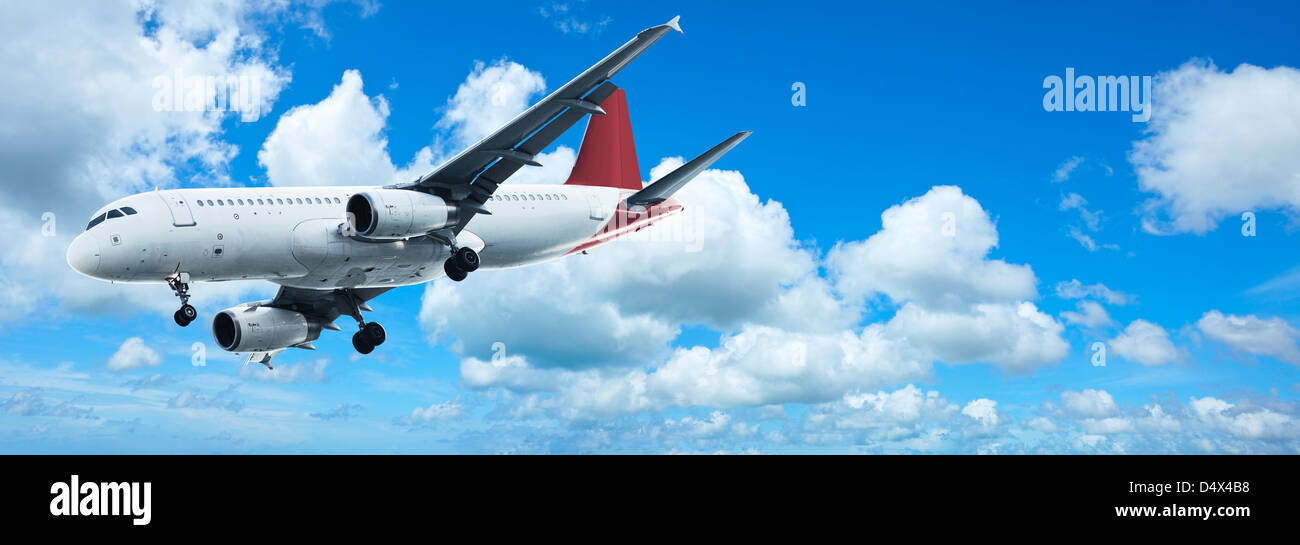 Jet plane in a blue sky. Panoramic composition. - Stock Image