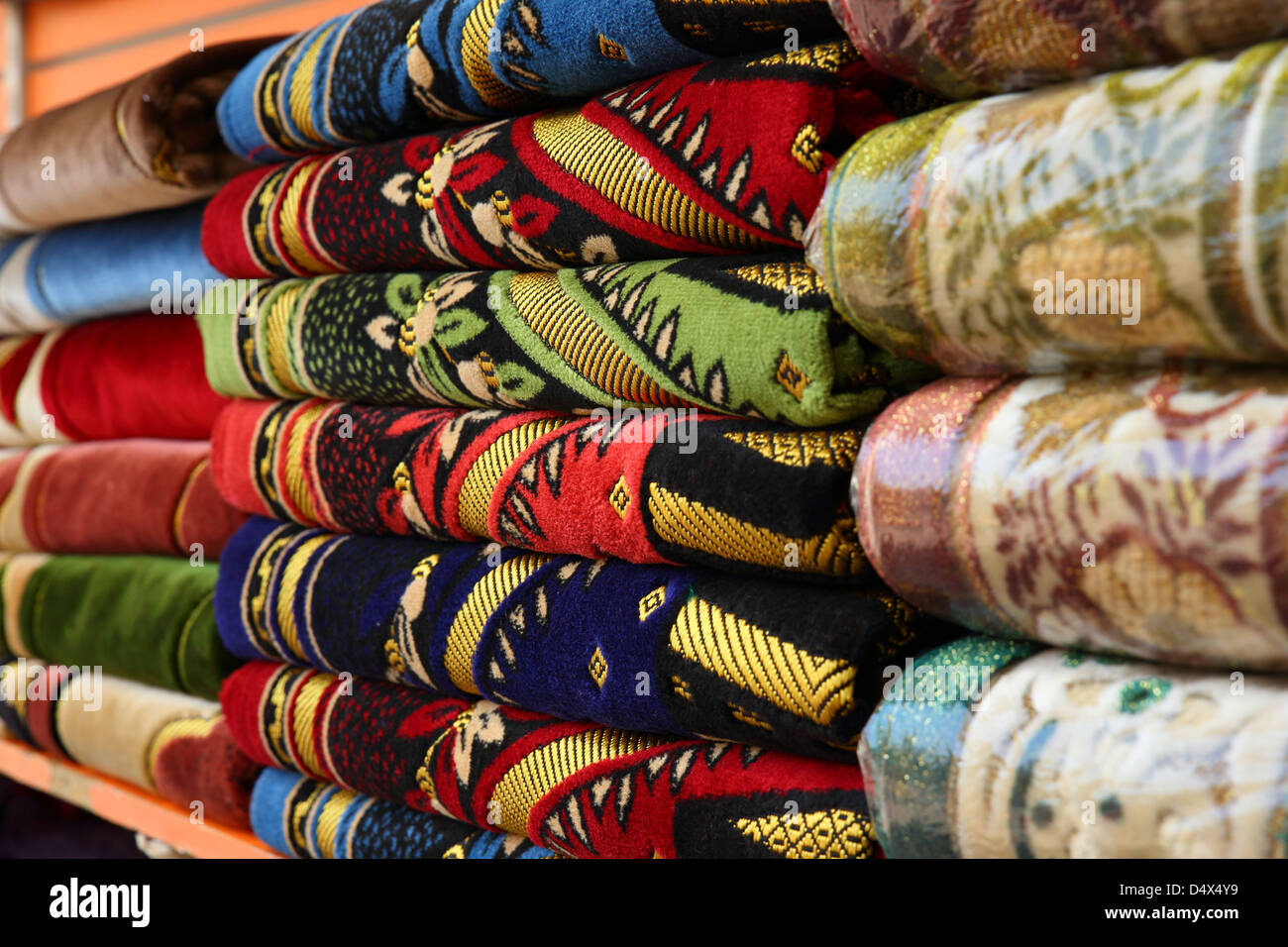 Closeup shot of ornate rugs and textiles at market in Dubai, United Arab Emirates - Stock Image
