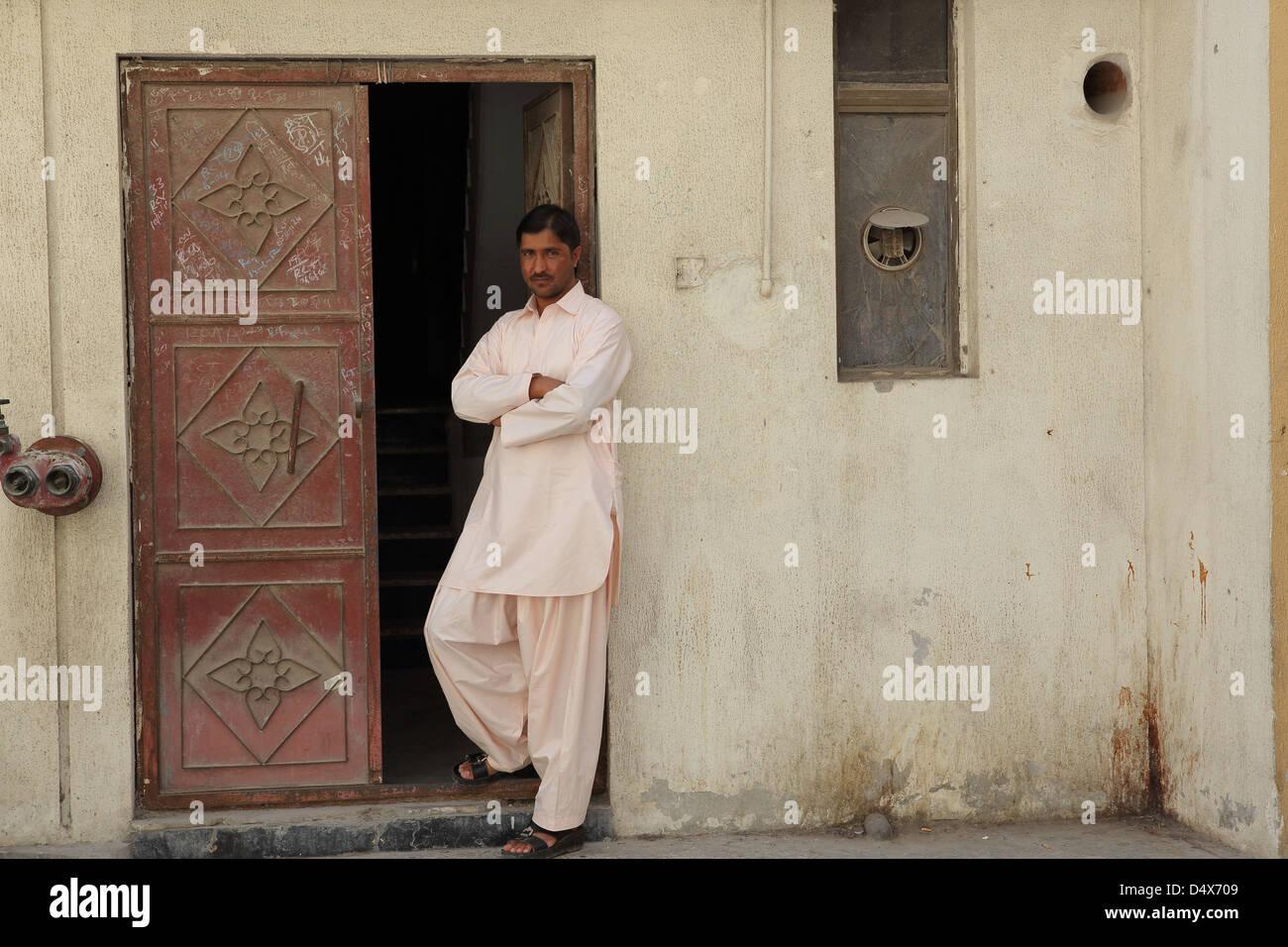Portrait of man standing in doorway, Dubai, United Arab Emirates - Stock Image