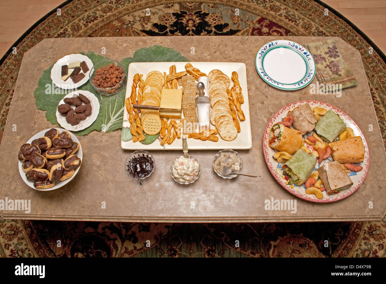 Table of eclairs, sandwich rolls, candy, cheese, crackers and herring snacks and appetizers. St Paul Minnesota MN - Stock Image
