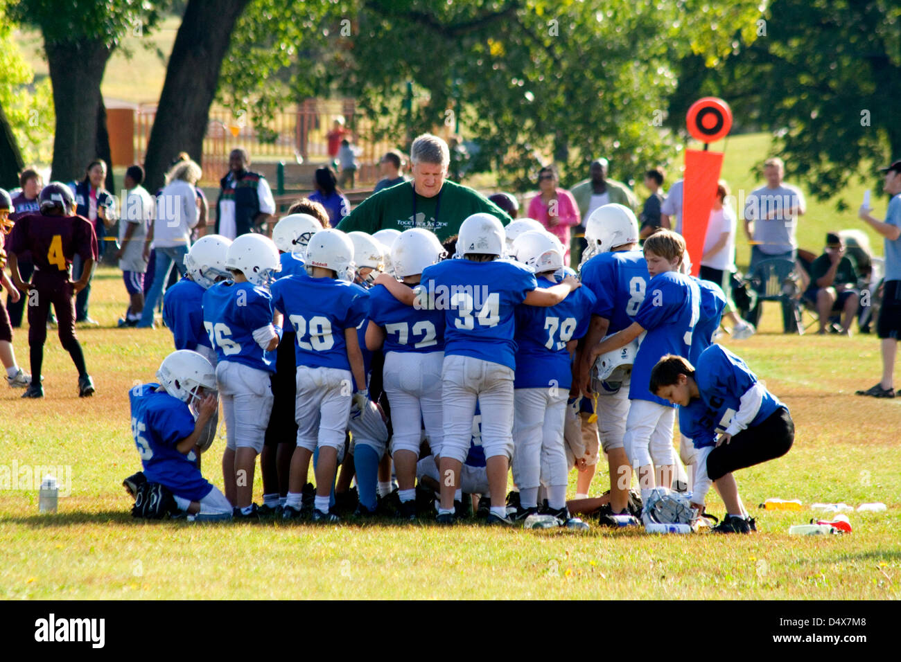 Young football players age 10 huddling around coach listening to his instructions. St Paul Minnesota MN USA - Stock Image